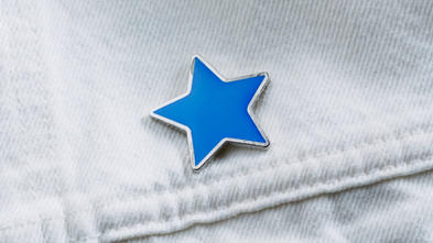 Blue enamel star-shaped pin on denim pocket